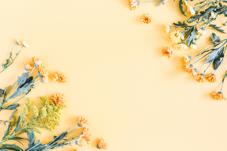 Autumn floral composition. Frame made of fresh flowers on pastel yellow background. Autumn, fall concept. Flat lay, top view, copy space