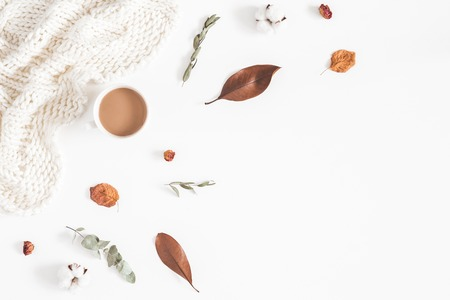 Autumn or winter composition. Cup of coffee, dried autumn leaves, knitted blanket on white background. Flat lay, top view Stock Photo