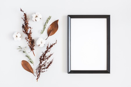 Autumn composition. Photo frame, dried flowers and leaves on white background. Autumn, fall concept. Flat lay, top view, copy space Stock Photo