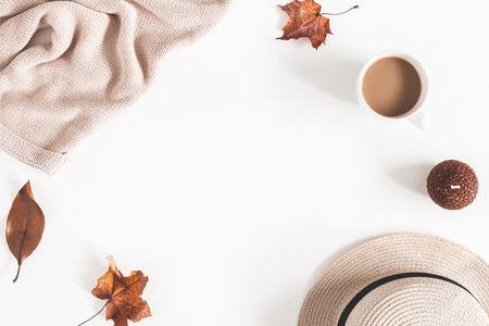 Autumn composition. Cup of coffee, hat, dried autumn leaves, beige sweater on white background. Flat lay, top view, copy space Фото со стока