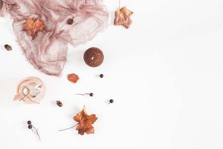 Autumn composition. Brown fabric, autumn flowers and leaves on white background. Flat lay, top view, copy space Stock Photo