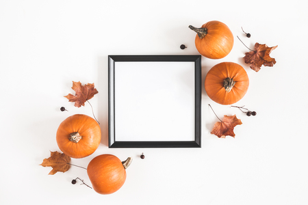 Autumn composition. Photo frame, pumpkins, dried leaves on white background. Autumn, fall, halloween concept. Flat lay, top view, copy space, square Foto de archivo - 107490506