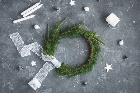 Christmas composition. Handmade christmas wreath, white decorations on dark background. Top view, flat lay