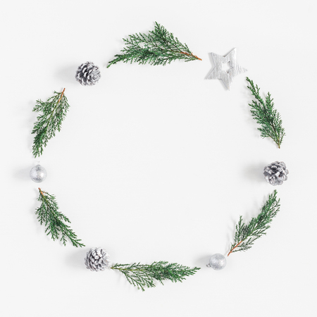 Christmas composition. Wreath made of christmas tree branches and silver decorations on white background. Flat lay, top view, copy space, square Stock Photo
