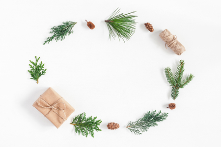 Christmas composition. Frame made of christmas gift, pine cones, winter plants on white background. Flat lay, top view, copy space
