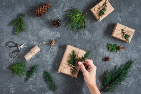 Christmas workspace. Girls hands making christmas gifts on black background. Flat lay, top view Stock Photo
