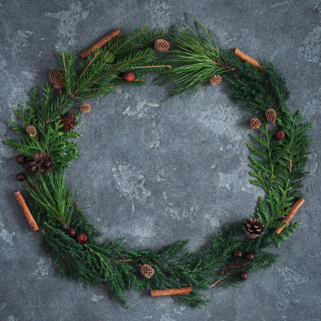 Christmas composition. Wreath made of different winter plants on black background. Christmas, winter, new year concept. Flat lay, top view, copy space, square