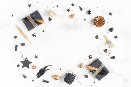 Christmas composition. Christmas gifts, pine cones, black and golden decorations on white background. Flat lay, top view Stock Photo