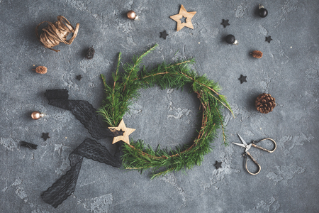 Christmas composition. Handmade christmas wreath, golden and black decorations on dark background. Top view, flat lay