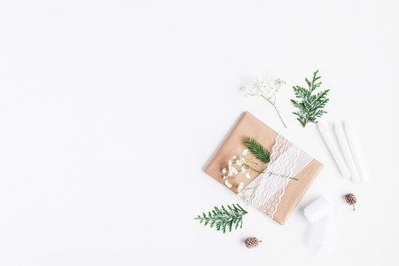 Christmas composition. Christmas gift, pine cones, gypsophila flowers, thuja branches on white background. Flat lay, top view, copy space