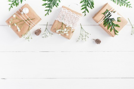 Christmas border. Christmas gifts, pine cones, gypsophila flowers, thuja branches on white wooden background. Flat lay, top view, copy space