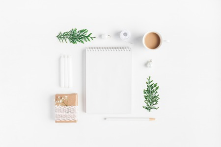 Cup of coffee, notebook, thuja branches on white background. Flat lay, top view, copy space