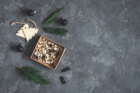 Cypress branches and wooden christmas decorations on dark background. Flat lay, top view, copy space Stock Photo
