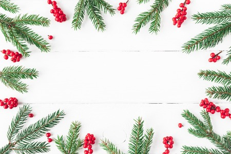 Christmas composition. Christmas frame made of fir tree branches and red berries on white background. Flat lay, top view, copy space Stok Fotoğraf