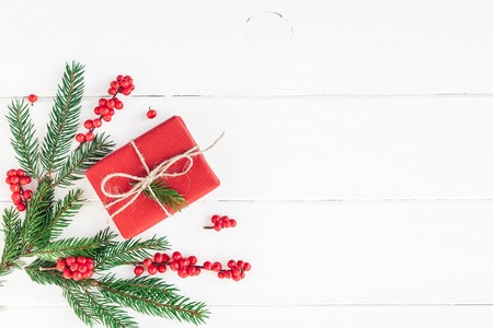 Christmas composition. Christmas gift, fir tree branches and red berries on white background. Flat lay, top view, copy space Stock Photo