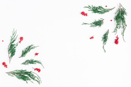 Frame made of christmas tree branches and red berries on white background. Flat lay, top view, copy space