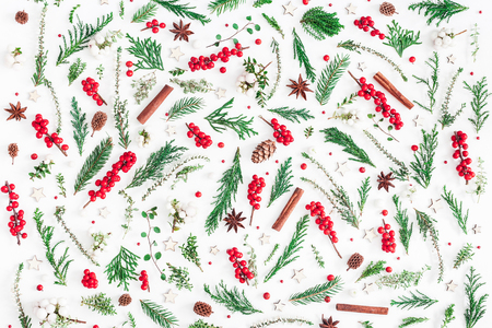 Christmas composition. Pattern made of christmas tree branches, red berries, cinnamon sticks, anise stars, decorations on white background. Flat lay, top view Stock Photo