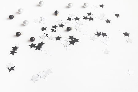 Christmas balls and paper confetti on white background. Front view, copy space