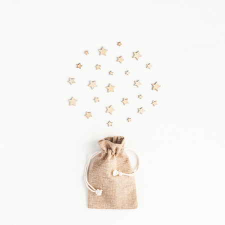Christmas composition. Christmas gift, wooden confetti on white background. Top view, flat lay, square