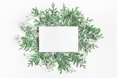 Christmas composition. Paper blank and thuja branches on white background. Flat lay, top view, copy space