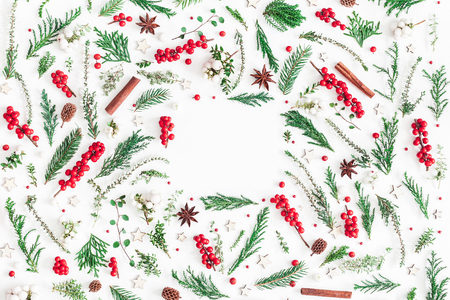 Christmas composition. Frame made of christmas tree branches, red berries, cinnamon sticks, anise stars, decorations on white background. Flat lay, top view, copy space Banco de Imagens