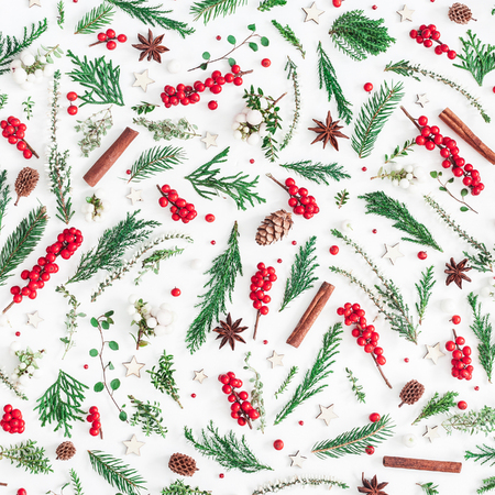 Christmas composition. Pattern made of christmas tree branches, red berries, cinnamon sticks, anise stars, decorations on white background. Flat lay, top view, square Standard-Bild