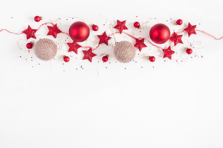 Weihnachtsgrenze. Weihnachtskugeln, Girlande, rote und goldene Dekorationen auf weißem Hintergrund. Flache Lage, Ansicht von oben, Kopienraum