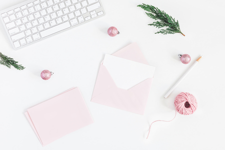 Christmas home office desk with computer, pink envelopes, pine branches, christmas decorations. Flat lay, top view, copy space Banco de Imagens