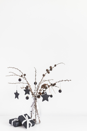 Christmas composition. Gifts, larch branches and black decorations on white background. Christmas, winter, new year concept. Front view, copy space