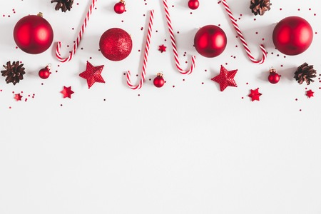 Christmas composition. Border made of red decorations on white background. Christmas, winter, new year concept. Flat lay, top view, copy space