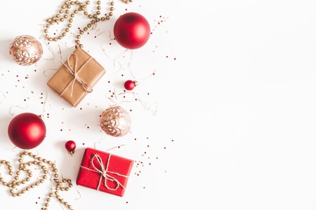 Christmas composition. Christmas gifts, red and golden decorations on white background. Flat lay, top view, copy space 写真素材