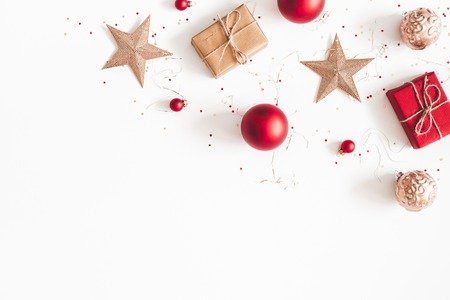 Christmas composition. Christmas gifts, red and golden decorations on white background. Flat lay, top view, copy space Imagens