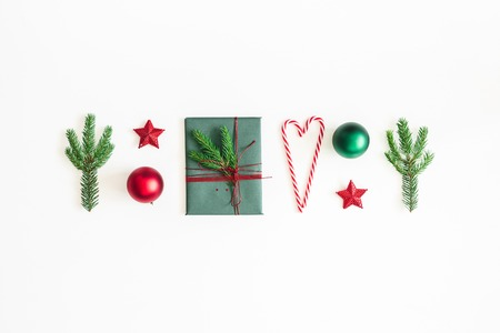 Christmas composition. Postcard, fir tree branches, red and green decorations on white background. Christmas, winter, new year concept. Flat lay, top view Stock Photo
