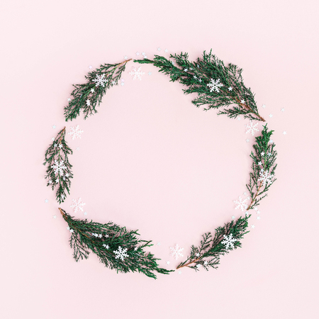 Christmas composition. Wreath made of fir tree branches, decorations on pastel pink background. Christmas, winter, new year concept. Flat lay, top view, square, copy space Stock Photo