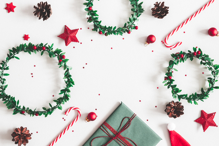 Composición navideña. Regalo, coronas, adornos rojos sobre fondo gris pastel. Navidad, invierno, concepto de año nuevo. Endecha plana, vista superior, espacio de copia Foto de archivo