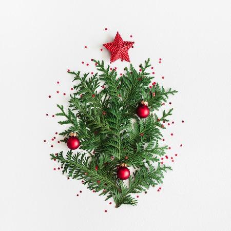 Weihnachtsbaum aus Nadelbaumzweigen auf pastellgrauem Hintergrund. Weihnachten, Winter, Neujahrskonzept. Flache Lage, Draufsicht, quadratisch,