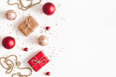 Weihnachtskomposition. Weihnachtsgeschenke, rote und goldene Dekorationen auf weißem Hintergrund. Flache Lage, Ansicht von oben, Kopienraum