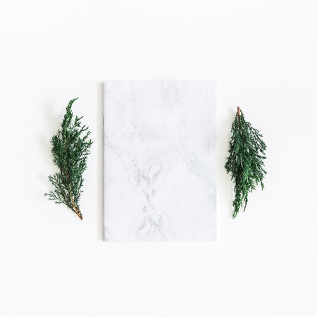 Christmas composition. Fir tree branches, marble notebook on white background. Christmas, winter, new year concept. Flat lay, top view, copy space, square 版權商用圖片