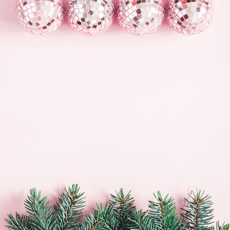 Christmas composition. Border made of fir tree branches, pink balls on pastel pink background. Christmas, winter, new year concept. Flat lay, top view, copy space, square