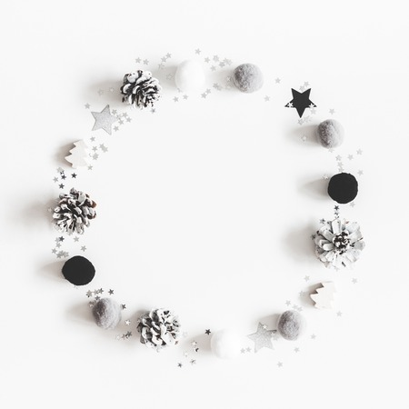Christmas composition. Wreath made of christmas black and silver decorations on pastel gray background. Flat lay, top view, copy space, square