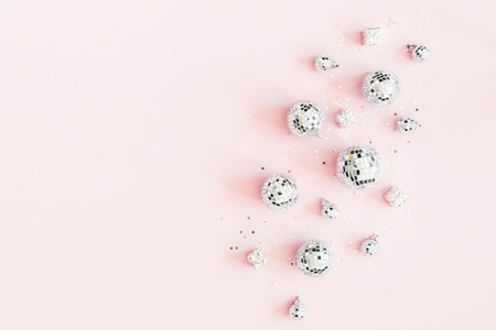 Christmas composition. Silver disco balls on pastel pink background. Christmas, winter, new year concept. Flat lay, top view, copy space