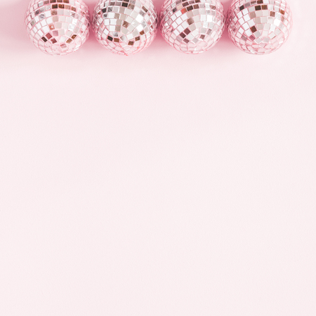 Christmas composition. Frame made of pink disco balls on pastel pink background. Christmas, winter, new year concept. Flat lay, top view, copy space, square