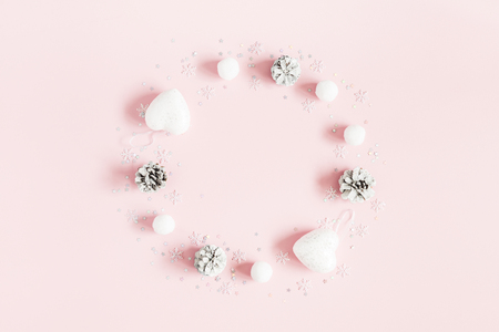 Christmas composition. Christmas wreath made of pink and white decorations on pastel pink background. Flat lay, top view, copy space