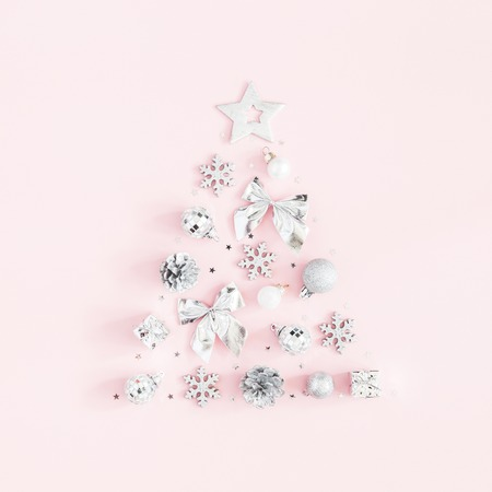 Christmas composition. Christmas tree made of silver decorations on pastel pink background. Flat lay, top view, square