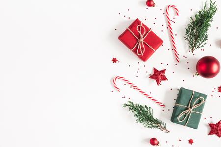 Kerst compositie. Geschenken, sparren takken, rode versieringen op witte achtergrond. Kerstmis, winter, nieuwjaarsconcept. Platliggend, bovenaanzicht, kopieerruimte