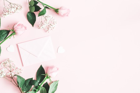 Valentines Day composition. Pink rose flowers, envelope on pastel pink background. Valentines day, mothers day, womens day concept. Flat lay, top view, copy space