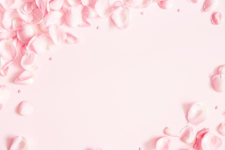 Composizione di fiori. Petali di fiori di rosa su sfondo rosa pastello. San Valentino, festa della mamma, concetto di festa della donna. Disposizione piana, vista dall'alto, copia spazio