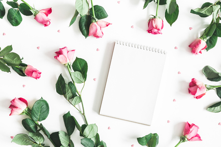 Flowers composition. Pink rose flowers, notebook on white background. Flat lay, top view, copy space Stock Photo