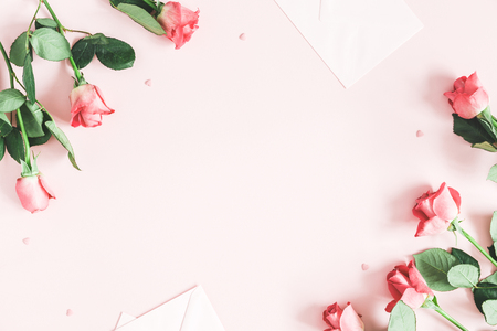 Flowers composition. Pink rose flowers, envelopes on pastel pink background. Valentines day, mothers day, womens day concept. Flat lay, top view, copy space