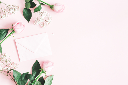 Valentines Day composition. Pink rose flowers, envelope on pastel pink background. Valentines day, Mothers day concept. Flat lay, top view, copy space